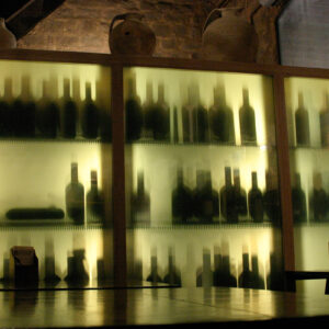 Sunlight casts shadows from bottles of Brunello di Montalcino in the castle enoteca, Montalcino, Tuscany